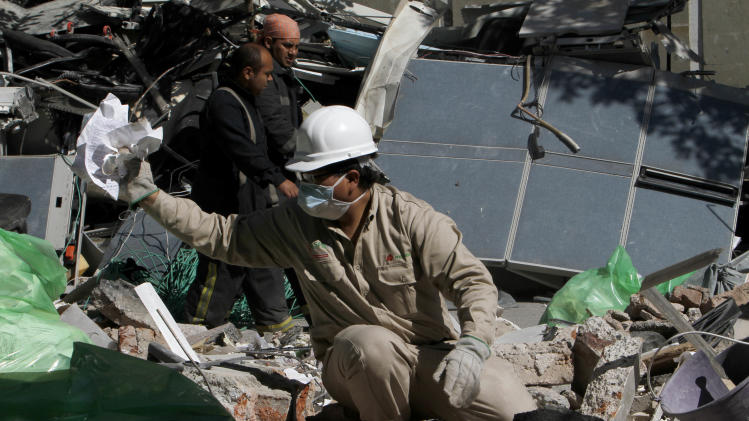An employee culls through debris searching for office documents amid the rubble left from an office building explosion, in Mexico City, Saturday, Feb. 2, 2013.  A Thursday blast collapsed the lower floors of the Mexican state-owned oil company Petroleos Mexicanos, or Pemex, headquarters, crushing at least 33 people beneath tons of rubble and injuring 121. A Pemex spokesman said the floors hit by the explosion housed administrative offices. (AP Photo/Marco Ugarte)