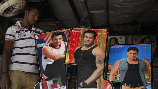 An Indian man displays photographs of Bollywood actor Salman Khan, custom made for decorating the interiors of auto-rickshaws in Ahmadabad, India, Wednesday, May 6, 2015. One of India's biggest and most popular movie stars, Khan, was sentenced to five years in jail Wednesday on charges of driving a vehicle over five men sleeping on a sidewalk and killing one in a hit-and-run case that has dragged for more than 12 years. (AP Photo/Ajit Solanki)