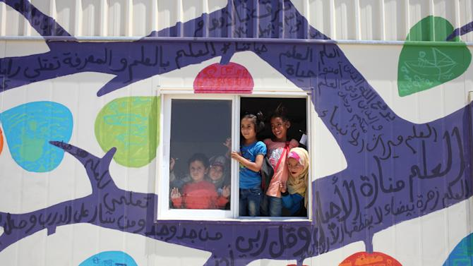 Syrian refugee children peer from the window of their classroom, newly decorated with a mural, at Zaatari refugee camp, near the Syrian border, in Mafraq, Jordan, Tuesday, July 23, 2013. Several writings in Arabic can be read on the mural, made up of old sayings and poetry that encourage the people to seek knowledge. Most of the trailers and tents match the beige color of the swirling sand surrounding the Zaatari refugee camp, home to about 120,000 Syrians who fled the nearly three-year war still gripping the nation. Slowly though, that's changing with the help of a U.S.-based artist who is leading children haunted by the conflict to paint buildings and walls at the crowded camp with murals expressing their lives and hopes. (AP Photo/Mohammad Hannon)