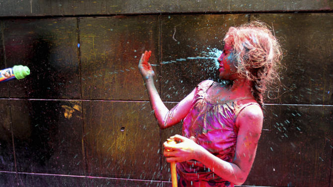 An Indian girl tries to block colored water being sprayed on her during Holi festival in Kolkata, India, Wednesday, March. 27, 2013. Holi, the Hindu festival of colors that also marks the advent of spring, is being celebrated across the country Wednesday. (AP Photo /Sucheta Das)