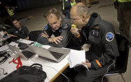 Solar Impulse pilots Bertrand Piccard, right, and Andre Borschberg, center, check the weather conditions before taking off at Barajas airport in Madrid, Spain, Tuesday, June 5, 2012. The experimental solar-powered airplane arrived in Madrid on May 25, 2012 from Payerne, Switzerland, and now goes on to Rabat, Morocco on its first transcontinental trip. The mission is described as the final dress rehearsal for a round-the-world flight with a new and improved aircraft in 2014. (AP Photo/Alberto Di Lolli)