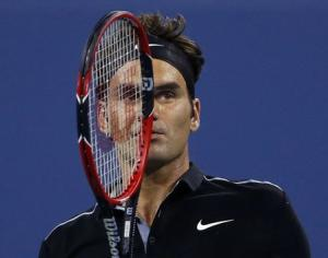 Roger Federer of Switzerland looks over at his opponent Roberto Bautista Agut of Spain during their men's singles match at the 2014 U.S. Open tennis tournament in New York