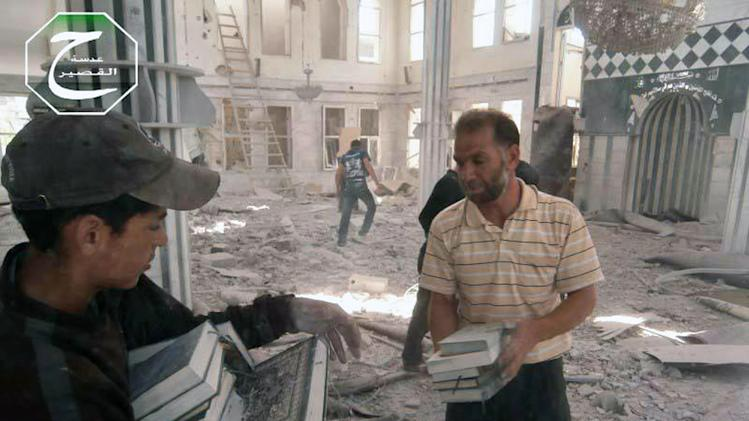 This citizen journalism image provided by Qusair Lens, which has been authenticated based on its contents and other AP reporting, shows Syrian men carrying copies of the Muslim holy book, the Quran, inside a bombed mosque in the town of Qusair near the Lebanon border, Homs province, Syria, Tuesday, May 21, 2013. Several members of Lebanon's militant Hezbollah group died of wounds sustained while fighting for control of a strategic Syrian town near the Lebanese border, activists said Tuesday, as the battle in the area raged for its third straight day. (AP Photo/Qusair Lens)