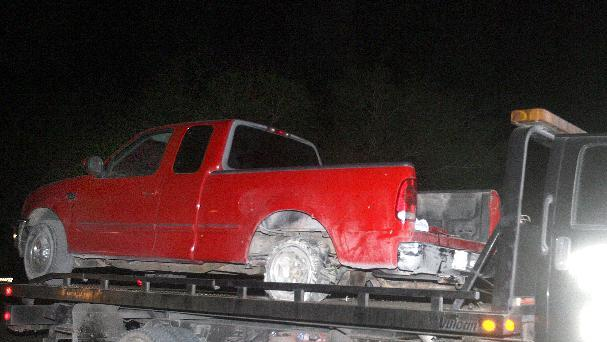 A red pick up truck is moved from the scene of a incident after a chase between law enforcement and suspected human smugglers on 7 mile road north of La Joya, Texas, Thursday, Oct. 25, 2012.  Texas Department of Public Safety sharpshooter opened fire on an evading vehicle loaded with suspected illegal immigrants, leaving at least two people dead, sources familiar with the investigation said.(AP Photo/The Monitor, Joel Martinez)