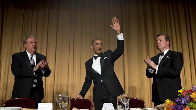 President Barack Obama, flanked by Michael Clemente, Executive Vice President of Fox News, left, and White House Correspondent Association President Ed Henry, Chief White House Correspondent for Fox News, right,  waves to the audience after speaking at the the White House Correspondents' Association Dinner at the Washington Hilton Hotel, Saturday, April 27, 2013, in Washington.  (AP Photo/Carolyn Kaster)