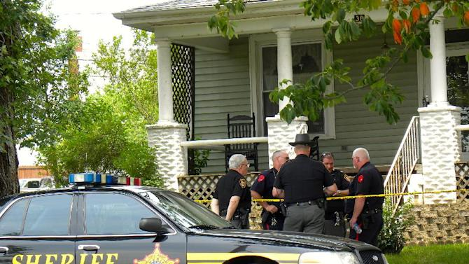 This photo made Wednesday, June 26, 2013, shows officials outside a home in Jackson, Ohio, where two boys, identified as 12-year-old Austin Wiseman and 9-year-old Blake Campbell, were found fatally shot Wednesday. (AP Photo/The Jackson County Times-Journal/www.JacksonCountyDaily.com, Jeremiah Shaver) MANDATORY CREDIT