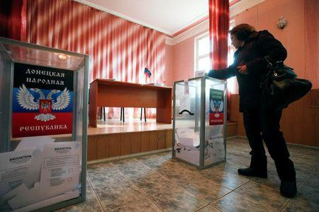 A woman casts a ballot during the self-proclaimed Donetsk People's Republic leadership and local parliamentary elections at a polling station in the coastal settlement of Sedovo