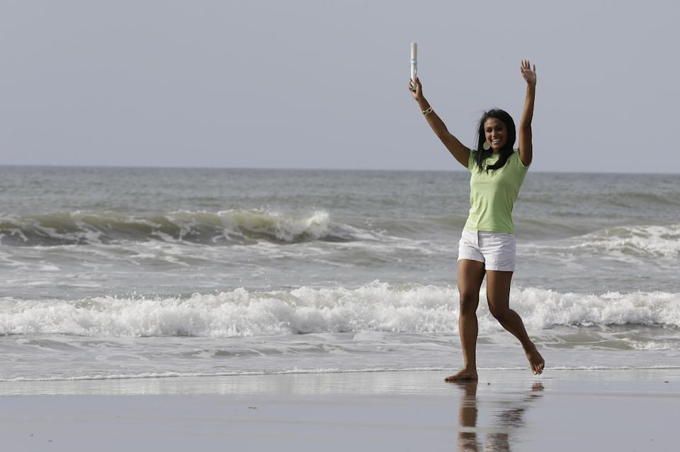 Miss America 2014 Nina Davuluri walks on the beach during the traditional dipping of the toes in the Atlantic Ocean the morning after being crowned Miss America, Monday, Sept. 16, 2013, in Atlantic City, N.J. Davuluri represented New York. (AP Photo/Julio Cortez)