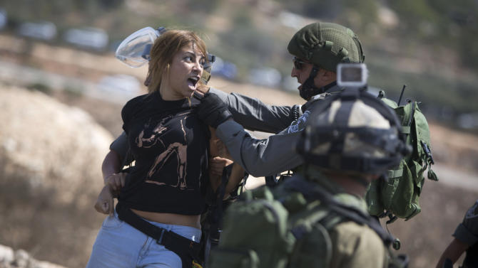 An Israeli border police officer detains a Palestinian woman, during a protest against the expansion of the nearby Jewish settlement of Halamish, in the West Bank village of Nabi Saleh near Ramallah, Friday, Sept. 4, 2015. (AP Photo/Majdi Mohammed)