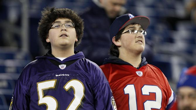 Brothers Cameron Ibarra, left, wearing the jersey of Baltimore Ravens inside linebacker Ray Lewis, and Sabastian Ibarra, right, wearing the jersey of New England Patriots quarterback Tom Brady, watch warm-ups before the NFL football AFC Championship football game between the Ravens and Patriots in Foxborough, Mass., Sunday, Jan. 20, 2013. (AP Photo/Stephan Savoia)