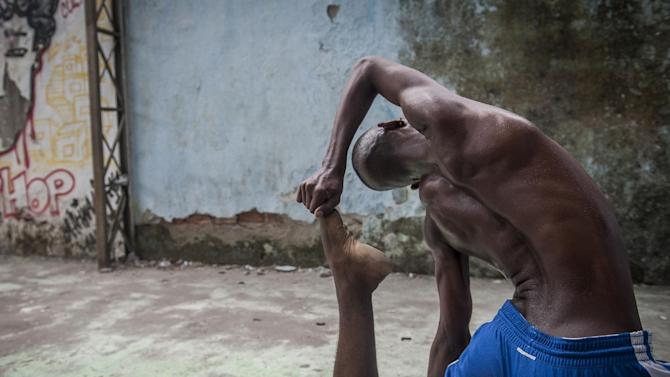 "In this Aug. 17, 2013 photo, Hilton Santos da Cruz Jr. practices during a ""passinho,"" or ""little step,"" session at a makeshift dance studio in the Borel favela, Rio de Janeiro, Brazil. The dance's popularity has benefited from a police crackdown on another late night activity, more raucous ""baile funk"" parties often organized by criminal gangs. In passinho gatherings, participants watch as performers square off against each other in choreographed duels. The dance's new superstars include Cruz, known as ""Hiltinho Fantastico"" or Fantastic Little Hilton. (AP Photo/Nicolas Tanner)"