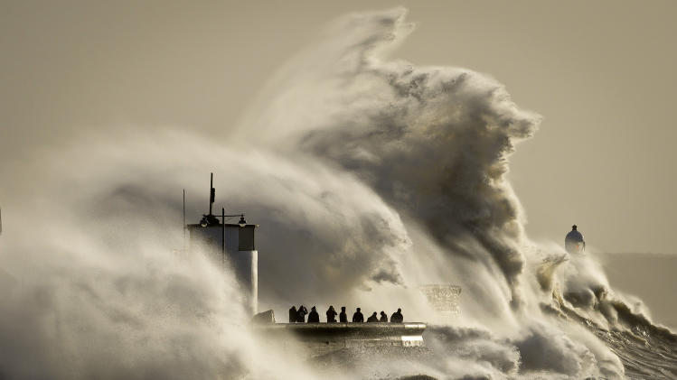 People watch and photograph enormous waves as they break, on Porthcawl harbour, South Wales, Monday Jan. 6, 2014. Residents along Britain's coasts are braced for more flooding as strong winds, rain and high tides lash the country. At least three people have died in a wave of stormy weather that has battered Britain since last week, including a man killed when his mobility scooter fell into a river in Oxford, southern England. (AP Photo/PA, Ben Birchall) UNITED KINGDOM OUT