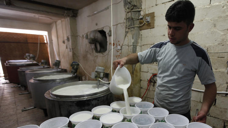 In this Sunday, Aug. 7, 2011 photo, a worker pours yogurt into containers at a small milk products factory in Fallujah, 40 miles (65 kilometers) west of Baghdad, Iraq. The U.S.-led invasion eight years ago provided an opportunity to liberate Iraqis not only from Saddam Hussein's oppression, but also from a command-and-control economy dependent on oil revenues. But when the last U.S. troops withdraw from Iraq by the end of the year, they will leave behind a nation in which widespread corruption, bureaucratic hurdles and electricity shortages continue to stifle the economy. (AP Photo/Hadi Mizban)