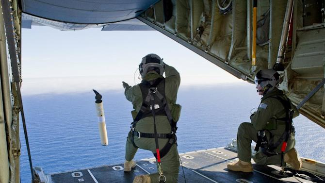 FILE - In this March 20, 2014 file photo provided by the Australia Defence Department, Royal Australian Air Force Loadmasters Sgt. Adam Roberts, left, and Flight Sgt. John Mancey, launch a Self Locating Data Marker Buoy from a C-130J Hercules aircraft in the southern Indian Ocean as part of the Australian Defence Force's assistance to the search for Malaysia Airlines flight MH370. The disappearance of the airplane has presented two tales of modern technology. The public has been surprised to learn of the limitations of tracking and communications devices, which contributed to the plane vanishing for more than two weeks. But the advanced capabilities of some technologies, particularly satellites, have provided hope that the mystery won't go unsolved. (AP Photo/Australian Defence Department, Justin Brown, File)
