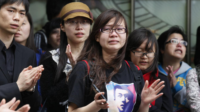 A tearful fan, center, along with others sings a song of the late Hong Kong actor-singer Leslie Cheung outside a hotel where Cheung jumped to his death, in Hong Kong Monday, April 1, 2013. Cheung's fans placed flowers to mark the 10th anniversary of the death of Hong Kong screen and singing legend Cheung. (AP Photo/Kin Cheung)