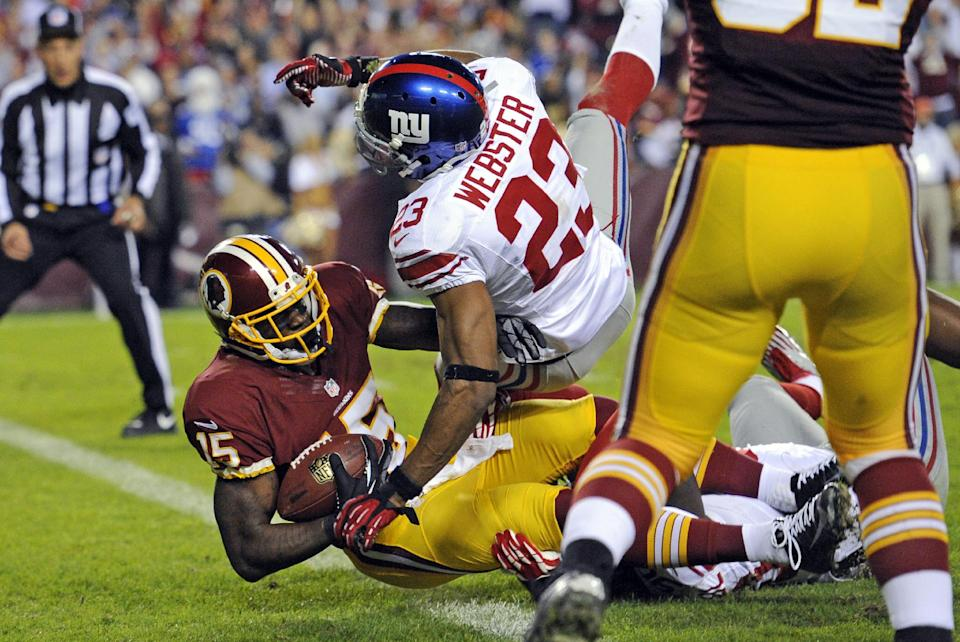 Washington Redskins wide receiver Josh Morgan (15) falls into the end zone for a touchdown under pressure from New York Giants cornerback Corey Webster (23) during the first half of an NFL football game in Landover, Md., Monday, Dec. 3, 2012. (AP Photo/Nick Wass)