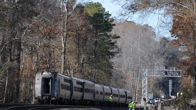 Workers are on the scene near the Amtrak Crescent train after it derailed, Monday, Nov. 25, 2013, in Spartanburg County, S.C. Several cars of the New York City-bound train with 218 people aboard went off the tracks early Monday as bags flew and jolted passengers clung to each other, authorities and passengers said. There were no serious injuries. (AP Photo/Rainier Ehrhardt)