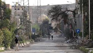 People walk along damaged street in Deir al-Zor, eastern Syria