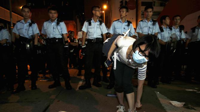 Pro-democracy protester puts on her lost shoe in front of a line of policemen during a confrontation at Mongkok shopping district in Hong Kong