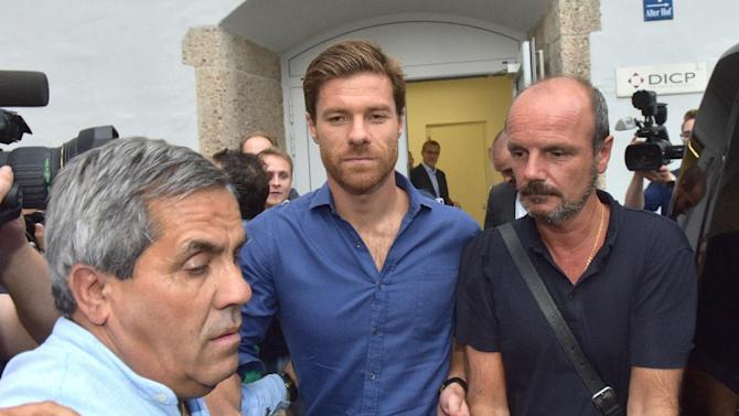 Spanish midfielder Xabi Alonso (C) of Real Madrid leaves after a medical checkup at a sports physician in Munich, southern Germany on August 28, 2014