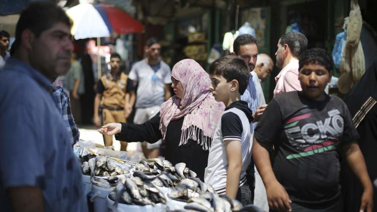Palestinians shop at a market in Khan Younis in the southern Gaza Strip