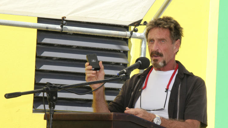 """FILE - In this Nov. 8, 2012 file photo, John McAfee speaks at a ceremony for the official presentation of equipment at the San Pedro Police Station in Ambergris Caye, Belize.  McAfee, 67, has been identified as a """"person of interest"""" in the killing of his neighbor, 52-year-old Gregory Faull. Police are urging McAffe to come in for questioning. The anti-virus company founder  said on Monday, Dec. 3, 2012, he has left Belize and is still on the run, hiding from police out of fear they want to kill him.  (AP Photo/Ambergris Today Online-Sofia Munoz, File)"""