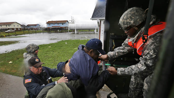 National Guard, Maryland State Police, and Crisfield police work together to assist a resident into a National Guard truck to be evacuated after the effects of superstorm Sandy, Tuesday, Oct. 30, 2012, in Crisfield, Md. (AP Photo/Alex Brandon)