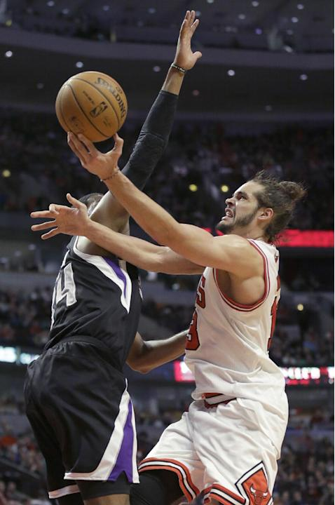 Chicago Bulls center Joakim Noah, right, drives to the basket against Sacramento Kings forward Jason Thompson during the second half of an NBA basketball game in Chicago on Saturday, March 15, 2014. T