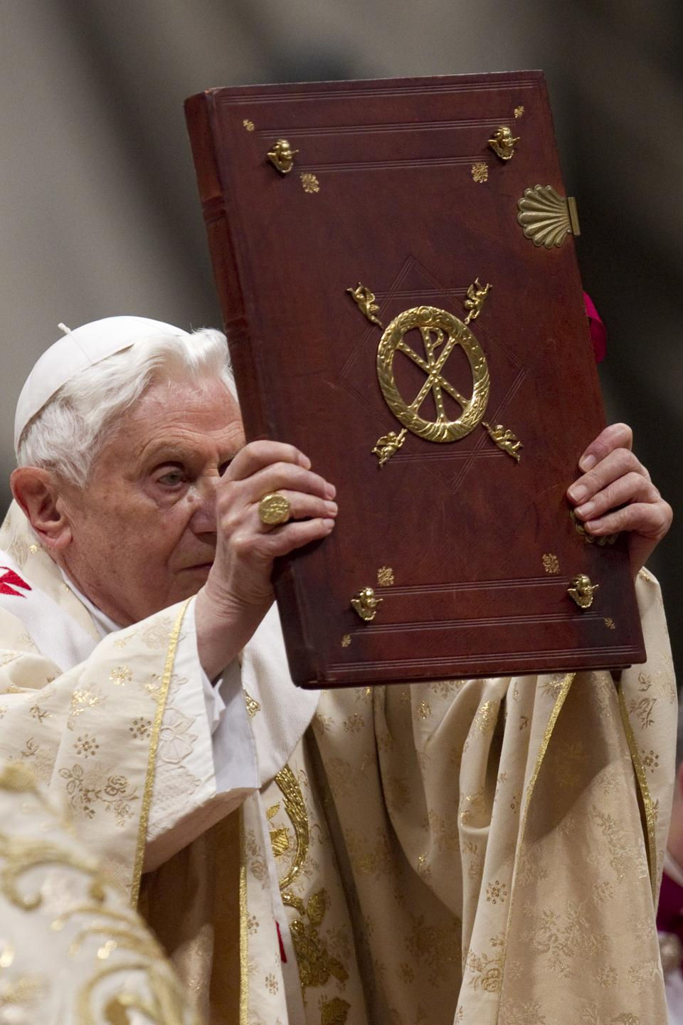 Pope Benedict XVI holds the Book of the Gospels as he celebrates Christmas Mass in St. Peter's Basilica at the Vatican, Saturday, Dec. 24, 2011. (AP Photo/Andrew Medichini)