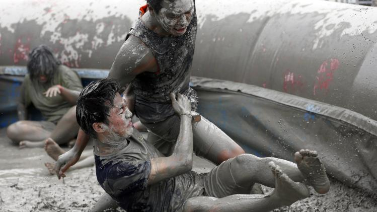 Tourists play in the mud during the Boryeong Mud Festival at Daecheon beach in Boryeong