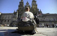 File photo shows a pilgrim resting in front of at the Santiago de Compostela Cathedral, at the end of the Way of Saint James. Spanish police have recovered a priceless 12th-century guide to Spain's Way of Saint James pilgrimage and arrested four people over its theft, officials said