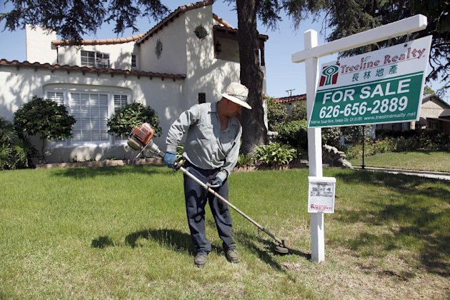 In this Monday, May 13, 2013 photo, gardener Jose Lopez trims the front lawn of a home for sale in Alhambra, Calif.  Freddie Mac reports on mortgage rates for the week on Thursday, May 23, 2013. (AP P