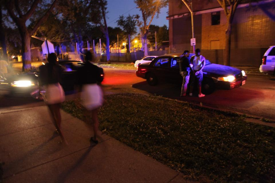 In a June 9, 2012 photo, residents stroll by as a young man is being arrested in Chicago. Homicides are up more than 50 percent over last year in Chicago. (AP Photo/Robert Ray)