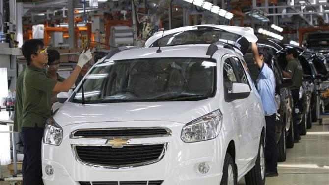 File photo of workers making final checks on new Chevrolet Spin MPVs at a General Motors plant in Bekasi