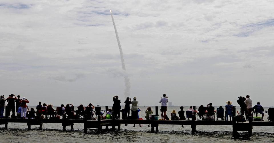 Spectators watch the final launch of space shuttle Atlantis in Titusville, Fla., Friday, July 8, 2011. Four astronauts are taking space shuttle Atlantis for one last ride, the very last one of the 30-year space shuttle era. (AP Photo/Gerry Broome)