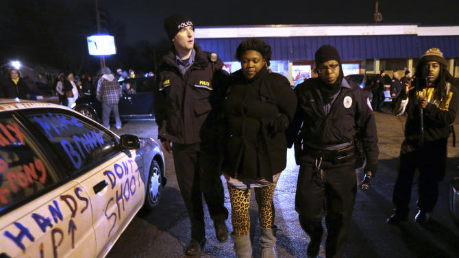 A woman walks with police near a gas station in Berkeley, Mo., on Wednesday, Dec. 24, 2014. The mayor of the St. Louis suburb of Berkeley urged calm Wednesday after a white police officer killed black 18-year-old Antonio Martin who police said pointed a gun at him, reigniting tensions that have lingered since the death of Michael Brown in neighboring Ferguson. (AP Photo/St. Louis Post-Dispatch, Robert Cohen)
