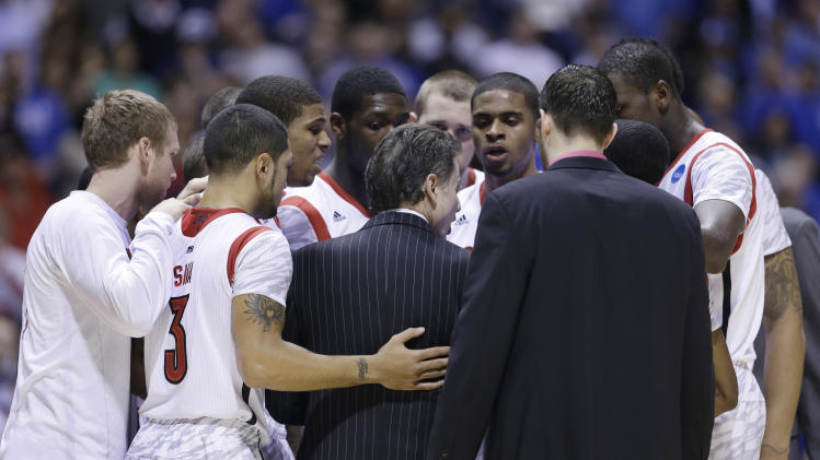 Louisville head coach Rick Pitino huddles with his team after Kevin Ware was taken out of the game following an injury during the first half of the Midwest Regional final against Duke in the NCAA college basketball tournament, Sunday, March 31, 2013, in Indianapolis. (AP Photo/Darron Cummings)