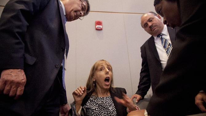 CODEPINK founder Medea Benjamin is surrounded by security as she shouts at President Barack Obama during his speech on national security, Thursday, May 23, 2013, at the National Defense University at Fort McNair in Washington. She was removed from the auditorium.  (AP Photo/Carolyn Kaster)