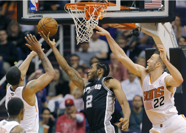 San Antonio Spurs' Kawhi Leonard (2) drives against Phoenix Suns' Miles Plumlee (22) during the second half of an NBA basketball game, Wednesday, Dec. 18, 2013, in Phoenix. The Spurs won 108-1