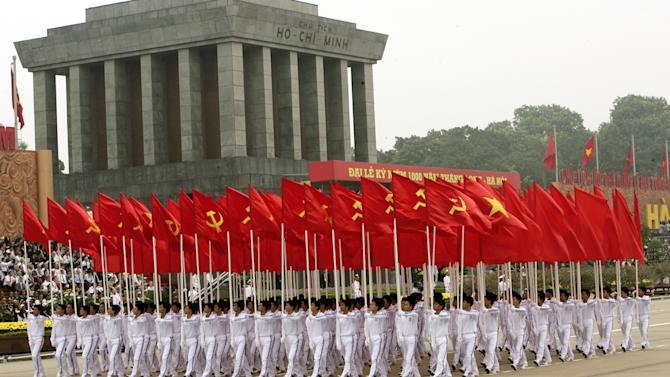 FILE - This Oct. 10, 2010 file photo shows men carrying Communist Party of Vietnam and national flags past the mausoleum of late Vietnamese President Ho Chi Minh during a parade in Hanoi, Vietnam. The embalmed body of Uncle Ho, as Vietnamese affectionately call their late founding president Ho Chi Minh, can be viewed inside an enormous granite mausoleum. For many Vietnamese, the trip to Hanoi to see the famous revolutionary who liberated them from French colonial rule is considered a must-do. The mausoleum offers regular changing of the guard ceremonies, but is only open during certain hours and days. (AP Photo/Tran Van Minh, file)