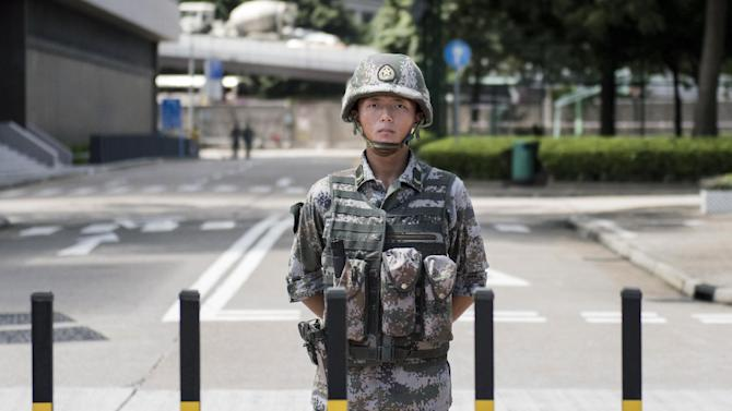 A Chinese People's Liberation Army soldier stands guard at the entrance to the PLA's Hong Kong Garrison headquarters on August 29, 2014