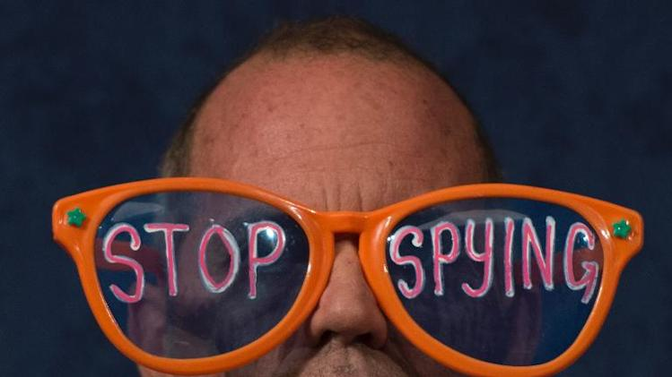 "A protester wears giant glasses with the message ""Stop Spying"" during a hearing on Capitol Hill in Washington, DC, October 29, 2013"