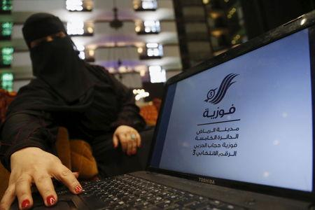 Saudi woman Fawzia al-Harbi, a candidate for local municipal council elections, shows her candidate biography at a shopping mall in Riyadh