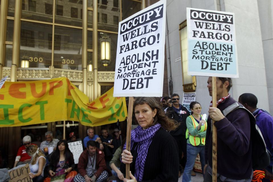 Demonstrators march and block a side entrance to the Wells Fargo shareholders meeting in San Francisco, Tuesday, April 24, 2012. Police guarded the entrance to the annual meeting of Wells Fargo shareholders on Tuesday as protesters associated with the Occupy Wall Street movement protested the gathering. (AP Photo/Marcio Jose Sanchez)