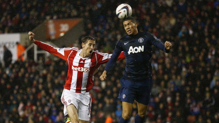 Manchester United's Smalling challenged by Stoke City's Crouch during their English League Cup quarter-final soccer match at the Britannia stadium in Stoke-on-Trent