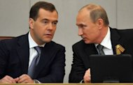 Former Russian President Dmirty Medvdev (L) speaks with Russian President Vladimir Putin (R) during a State Duma conference in Moscow. Russia's new President Vladimir Putin on Tuesday won parliamentary approval for his predecessor Dmitry Medvedev to become prime minister, as protesters tried new tactics to keep up pressure on the Kremlin
