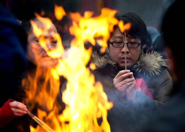 A Chinese man prays for health and fortune on the first day of the Lunar New Year at Yonghegong Lama Temple in Beijing Sunday, Feb. 10, 2013. Millions across China are celebrating the arrival of the L