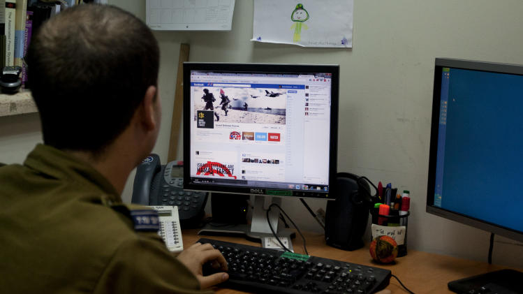 "FILE - In this Thursday, Nov. 15, 2012 file photograph, an Israeli soldier looks at the Facebook page of the Israel Defense Force, at the IDF spokesperson's office in Jerusalem. In a media bunker, attached to Israel's press office, hundreds of volunteers work around the clock on every major social media platform to produce and post instant videos and graphics about the latest twists in the Gaza offensive from Israel's point of view. Its Facebook site ""Israel Under Fire"" has gained more than 24,000 ""likes"" over the last week. (AP Photo/Sebastian Scheiner, File)"