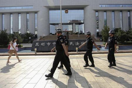 Policemen patrol as a woman walks past in front of a court, where a trial of suspects of the Kunming railway station attack is taking place, in Kunming