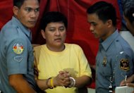 Detained Maguindanao massacre suspect Andal Ampatuan Jnr. (C) is escorted by policemen back to his cell in Manila. Andal Ampatuan Jnr, allegedly led his family&#39;s private army in stopping a convoy carrying the wife and relatives of a political rival, lawyers and a group of 32 journalists, and then gunning them down on a grassy hill
